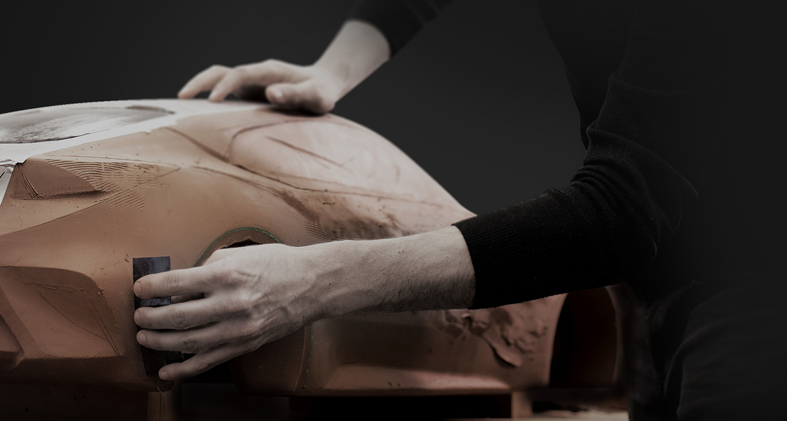Closer view at hands of a designer polishing  a 1/4 scale clay model with a black background