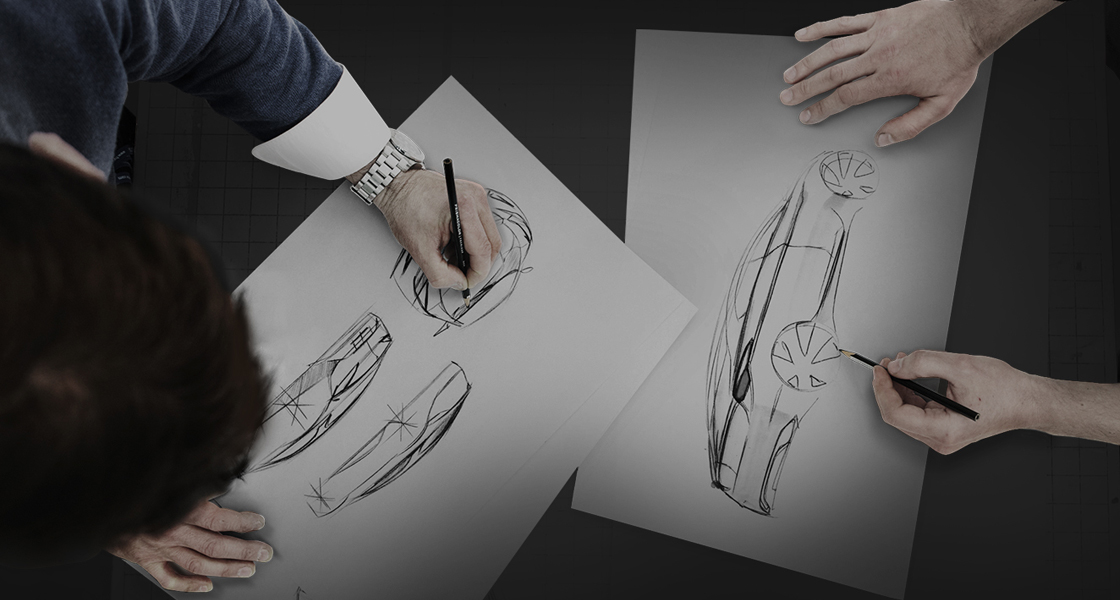view from the top at two designers sketching automobiles in a black background
