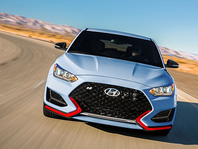 front view of blue veloster n driving on the countryside road