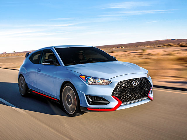 right side front view of blue veloster n driving on the countryside road