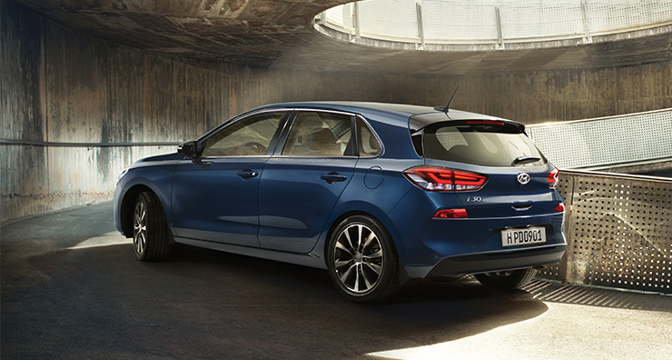 Left side rear view of blue i30 driving on the uphill road