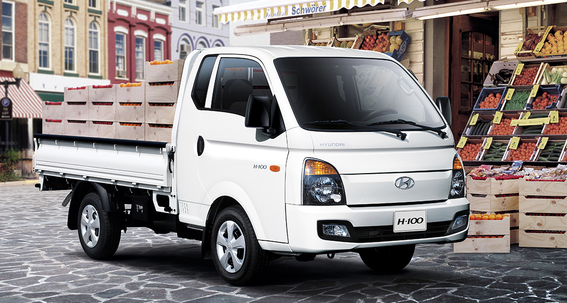 Side-front view of white H-100 parked in front of fruit market in the city