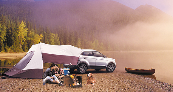 Family enjoying camping with a dog at lake with white Creta and tent