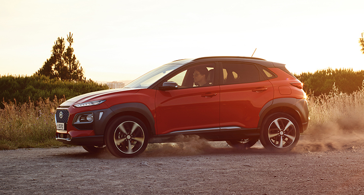 left side view of red kona driving on the outdoor field