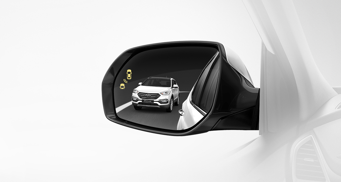 Blind spot detection activates on the side mirror with reflection of white Santa Fe approaching from behind