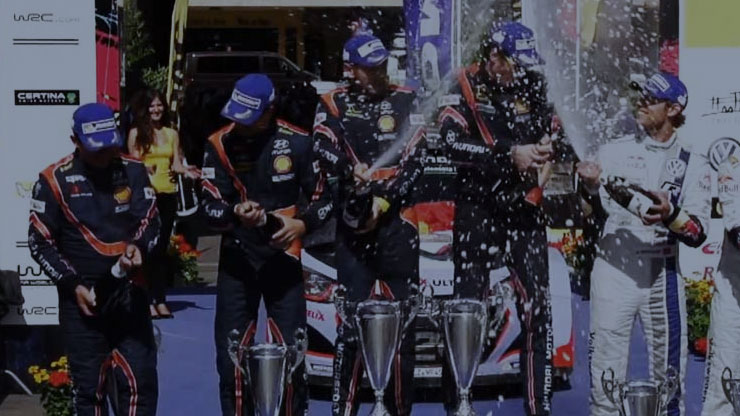 four hyundai drivers stand on the podium to celebrate with champagnes