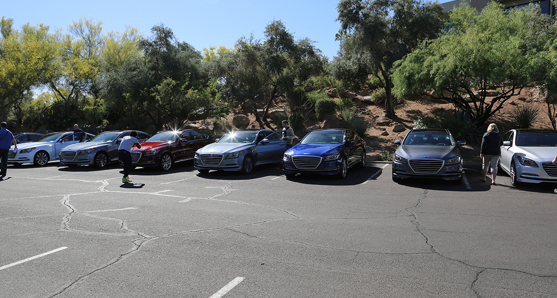 Front View Of Genesis Lined Up At The Test Drive Parking Lot With Trees Behind