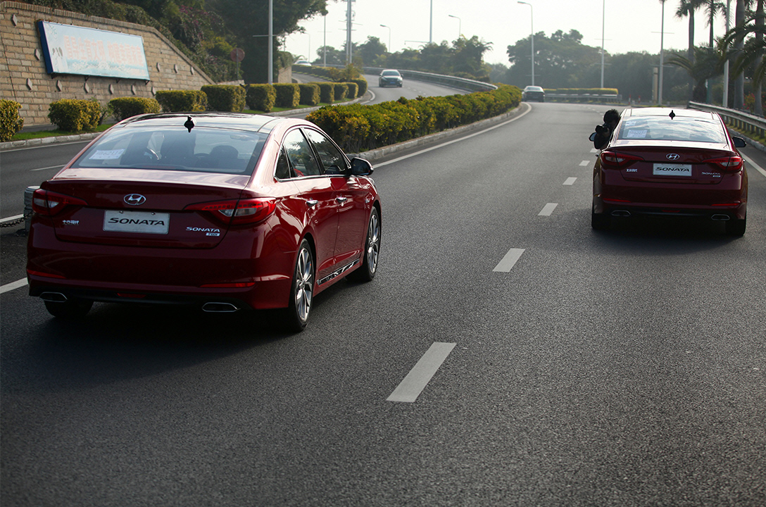Rear view of two red sonata cars driving on the road with the forest
