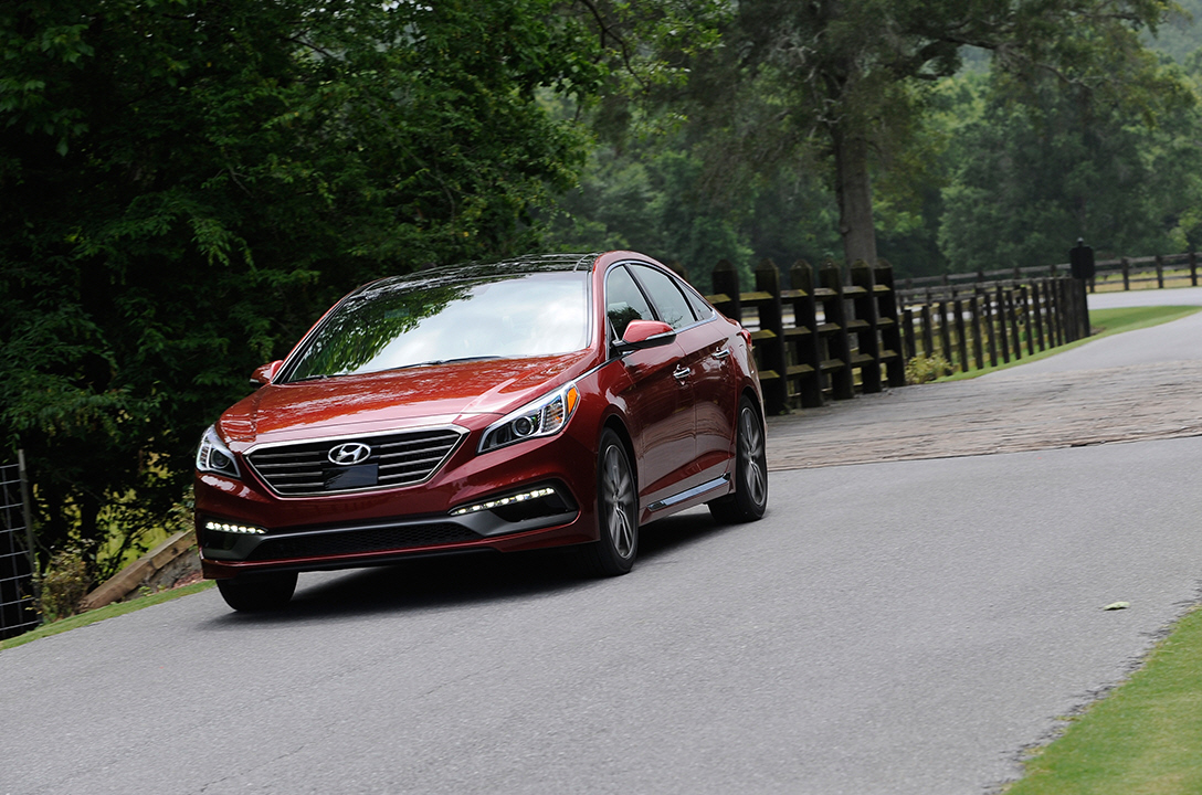 Left side-front view of red sonata driving on the road with the forest beside